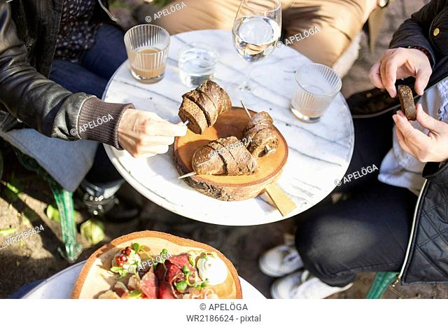 High angle view of hands holding bread slices at outdoor cafe