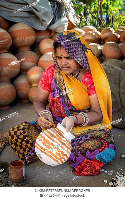A woman painting pots and water jugs at a pottery stall in Jaipur, Rajasthan, India