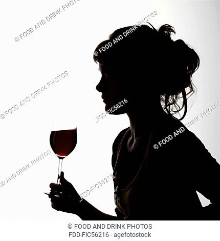 Silhouette portrait of a young woman enjoying a glass of red wine