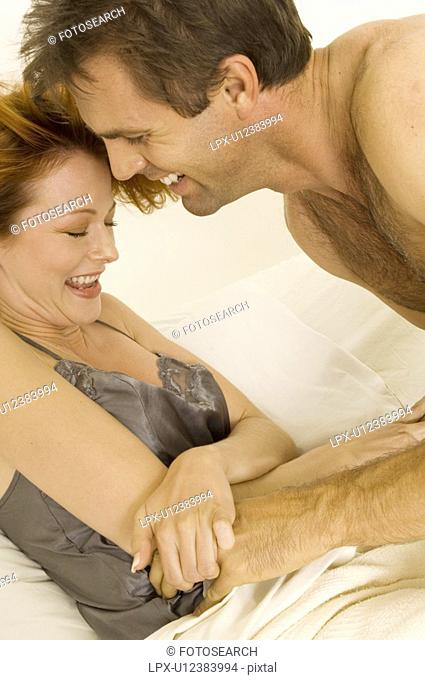 Portrait of a couple tickling each other in bed