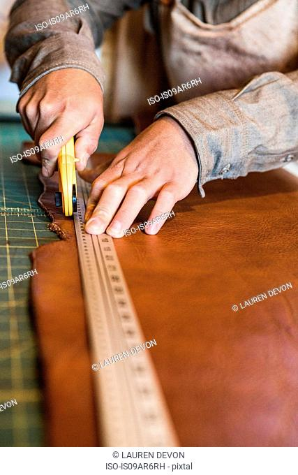 Hands of leather craftsman using rotary cutter on workshop bench