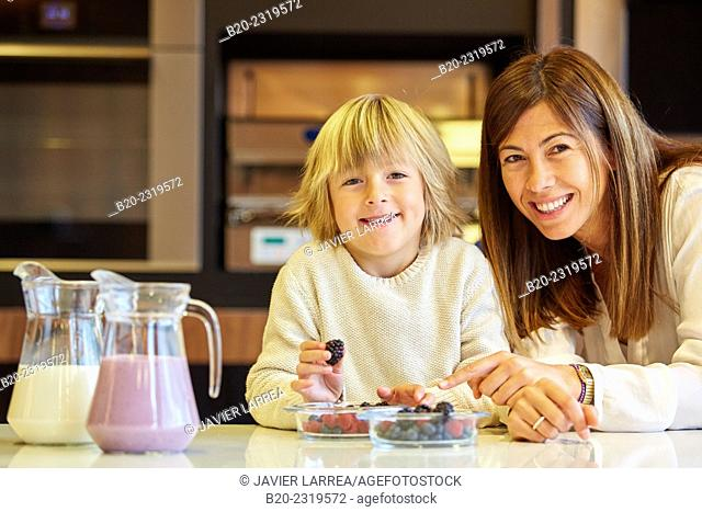 Family in the kitchen. Mother and son. Healthy eating. Healthy growth. Making milkshakes with berries