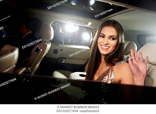 Dark haired young woman waving from the back of a limo