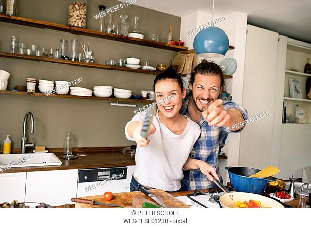 Young couple preparing food together, laughing and pointing with spatula