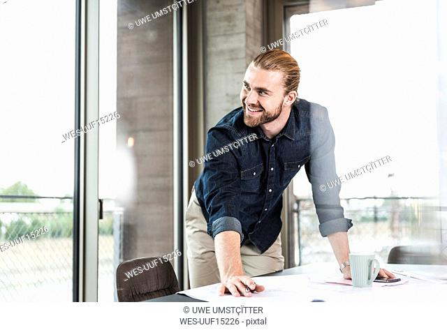 Smiling young businessman working on plan at desk in office