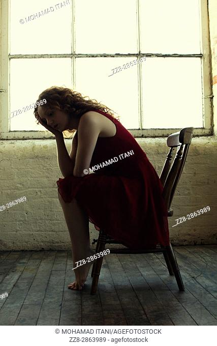 Miserable redhead woman sitting on a chair by the window