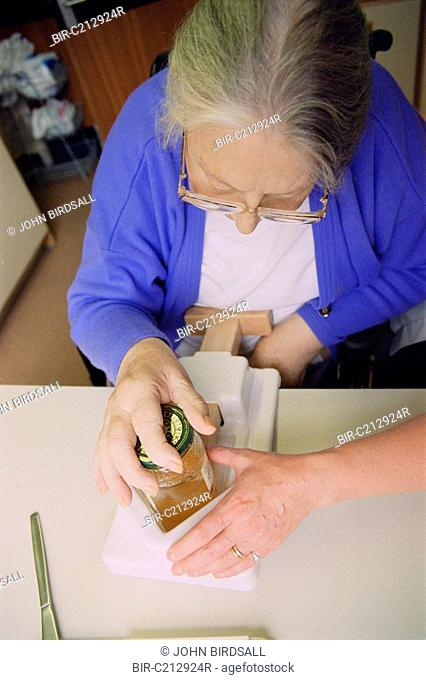 Occupational Therapy session with patient using Belliclamp to open a jar with one hand following stroke