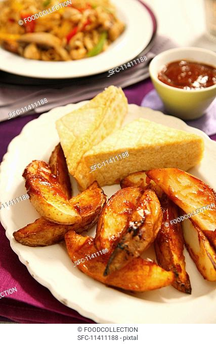Roast potato wedges with a chilli sauce and a piece of tofu