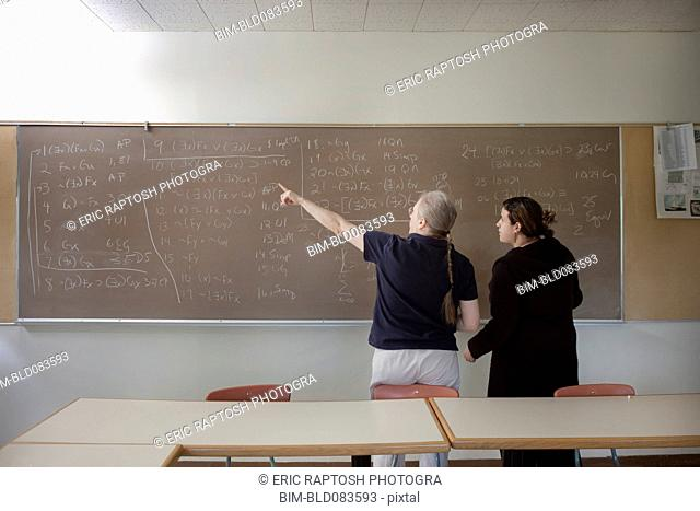 Teacher explaining arithmetic to student in classroom