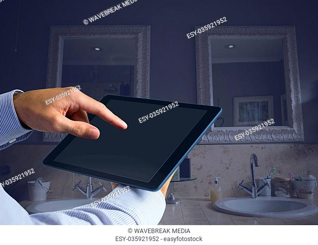 Hand holding tablet at home bathroom