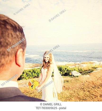 Groom looking at bride, sea in background