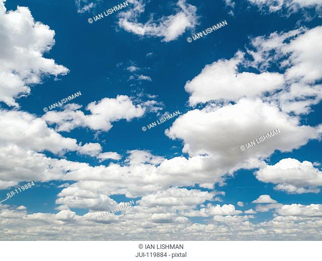 Blue sky background with fluffy white clouds
