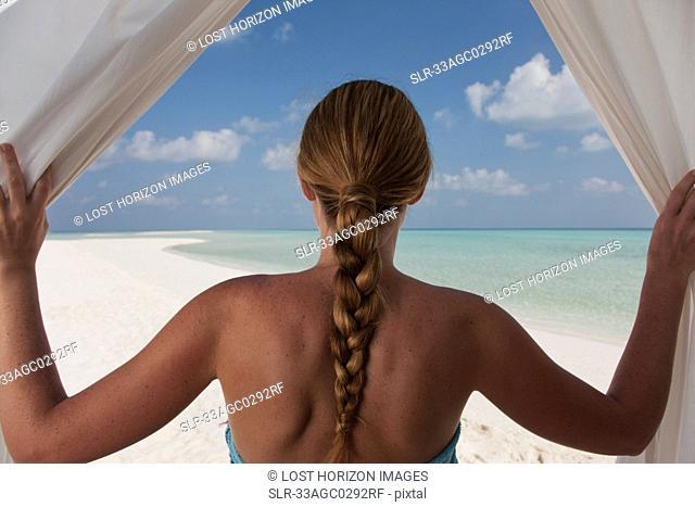 Woman admiring beach through curtains