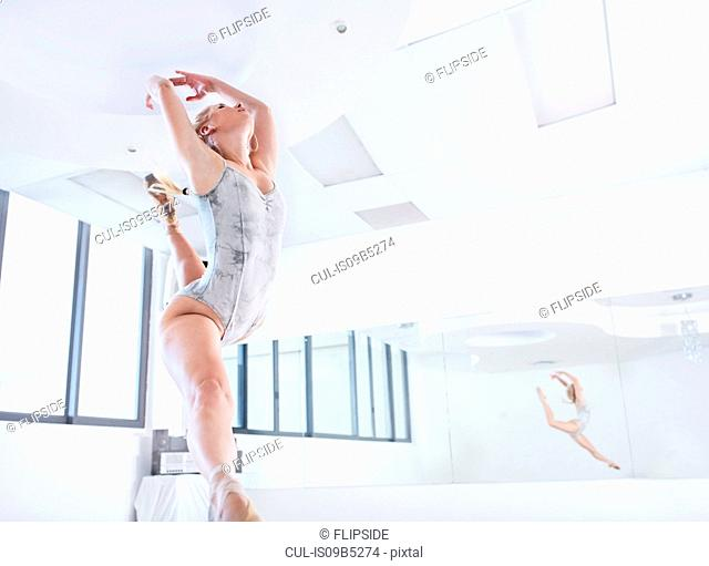 Young female ballet dancer leaping in dance studio