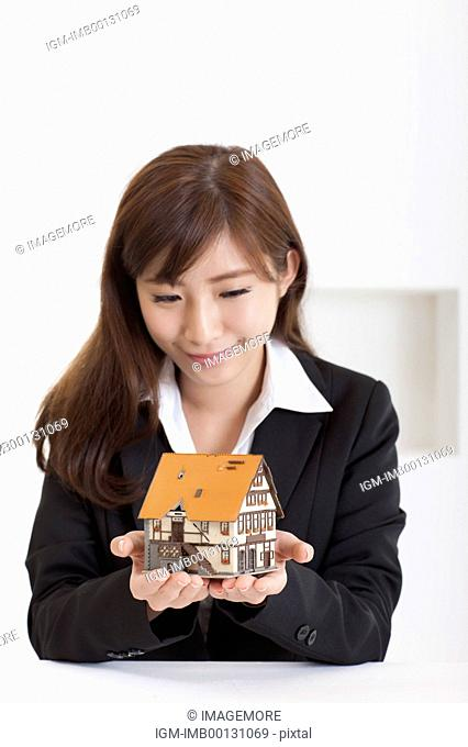 Young business woman holding house model and looking down with smile