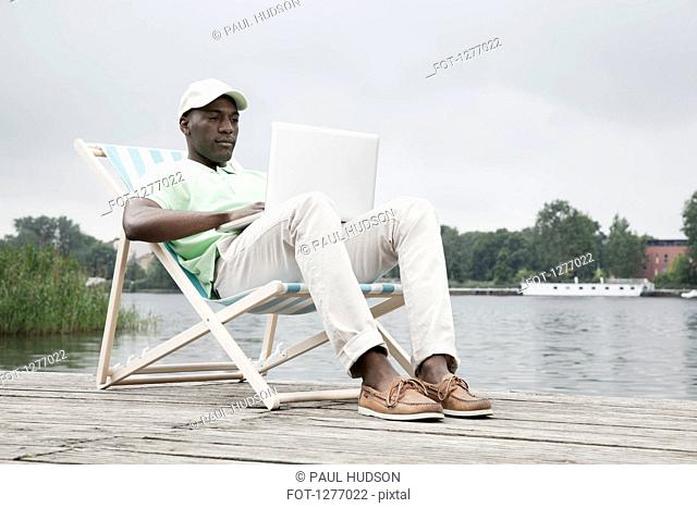 Man relaxing on deckchair with laptop by lake