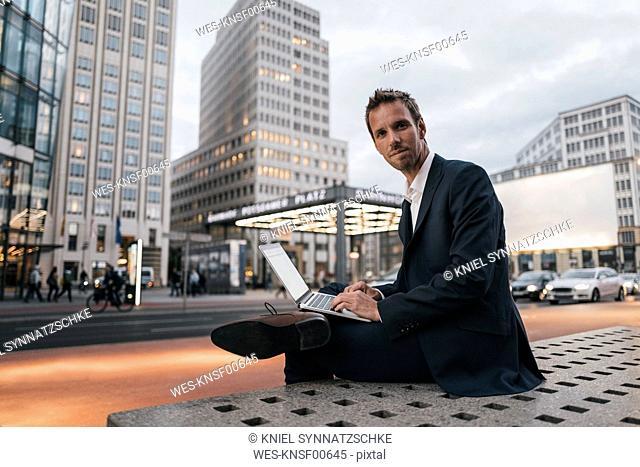 Germany, Berlin, Potsdamer Platz, portrait of businessman sitting on bench using laptop in the evening