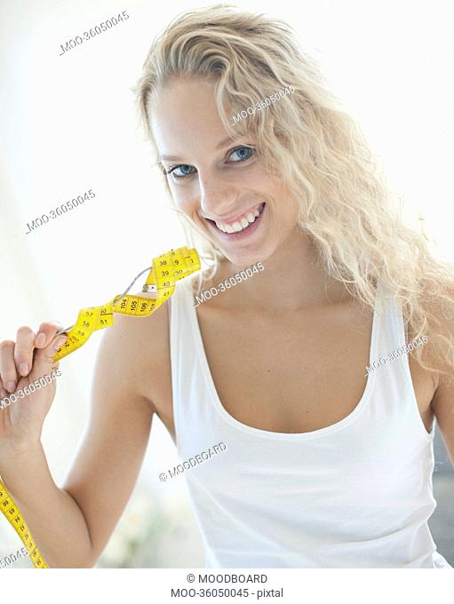 Portrait of happy woman holding fork wrapped with measuring tape