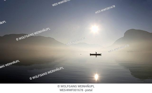Austria, Mondsee, View of fishing boat in lake with foggy morning