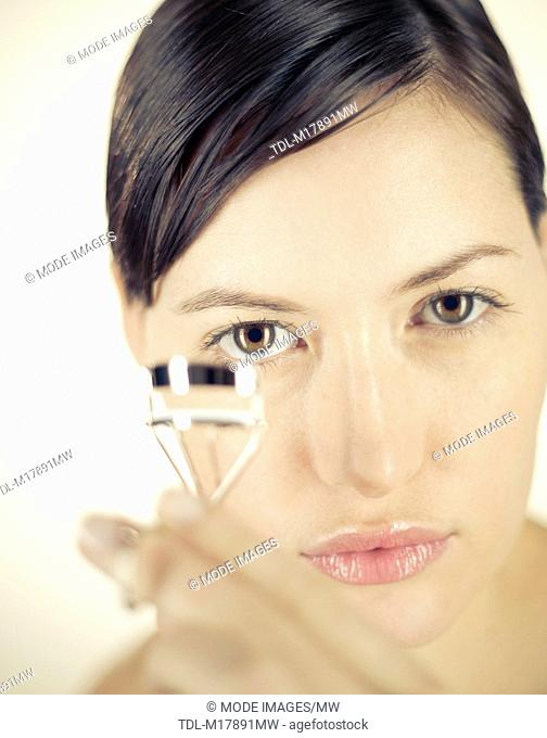 A young woman holding eyelash curlers