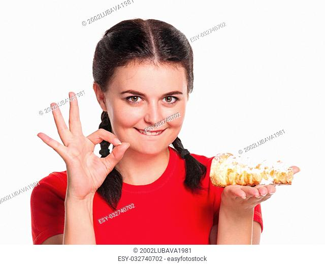 Young woman with tasty tubule cake shows OK gesture isolated over white