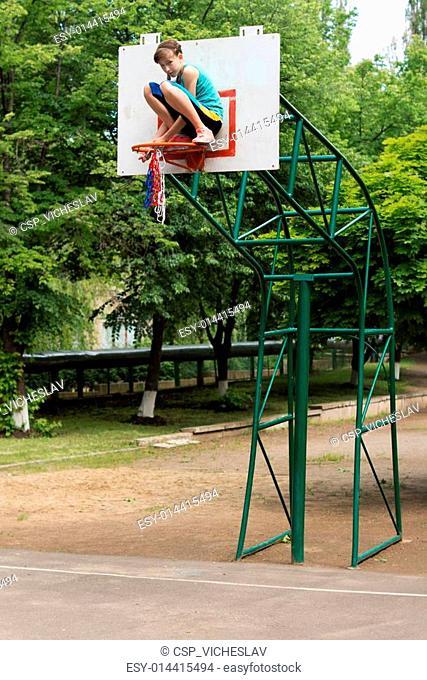 Young teenage girl fixing a basketball net