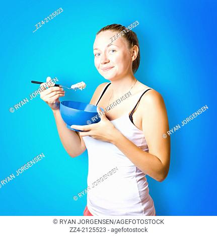 Cute female lifestyle model about to eat a bowl filled with oats and porridge on blue copyspace background