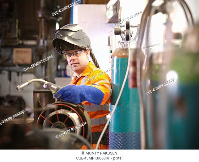 Apprentice engineer welding in factory