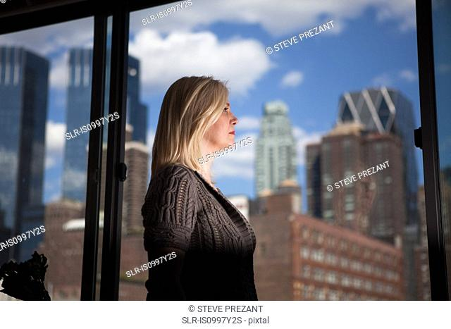 Mature woman staring out of an office block window at skyscrapers