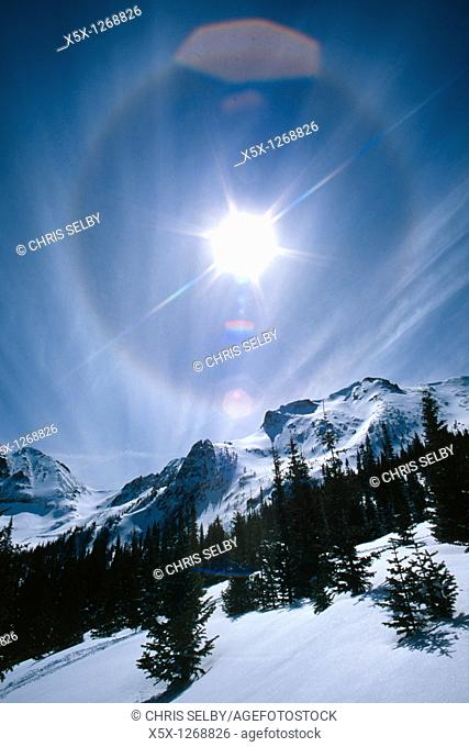 Sundog and lens flare in sky over Never Summer mountains in winter, Colorado, USA