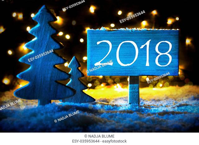 Sign With Text 2018 For Happy New Year. Blue Christmas Tree With Snow And Magic Glowing Lights In Backround. Card For Seasons Greetings