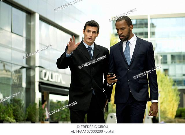 Businessmen walking and talking together outdoors