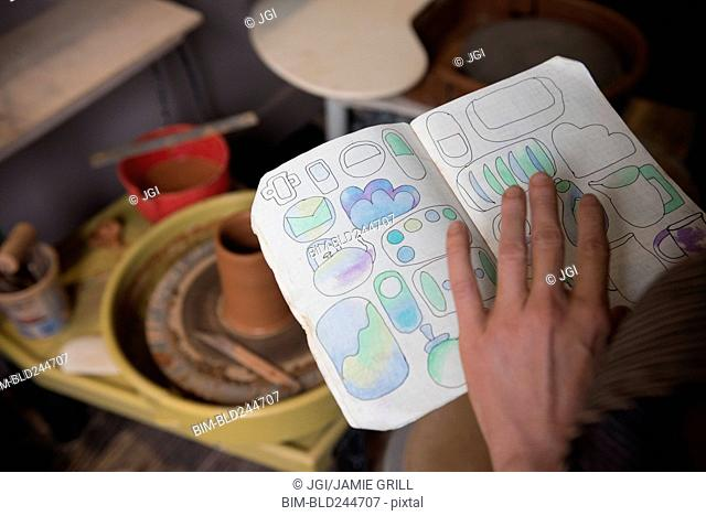 Hand of Caucasian woman examining drawings in book near pottery wheel