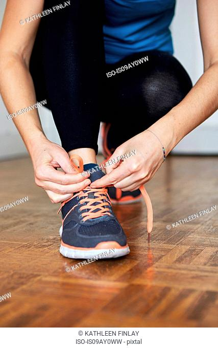 Low section of woman crouching tying shoelace on running shoe