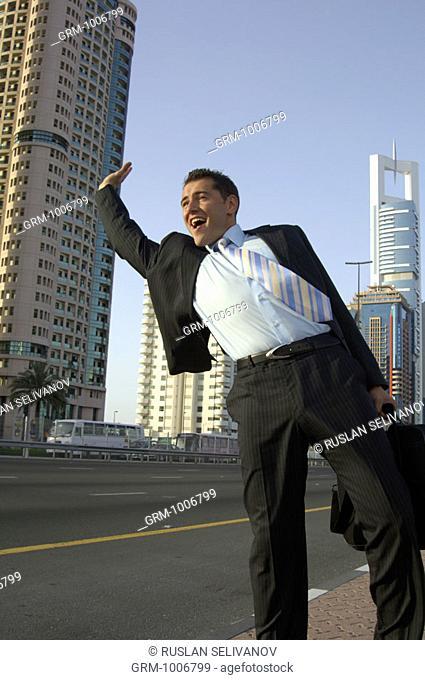 Businessman flagging down a cab on Shaikh Zayed Road in Dubai
