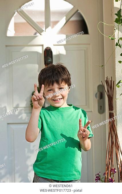 Germany, Bavaria, Boy showing peace sign, smiling, portrait