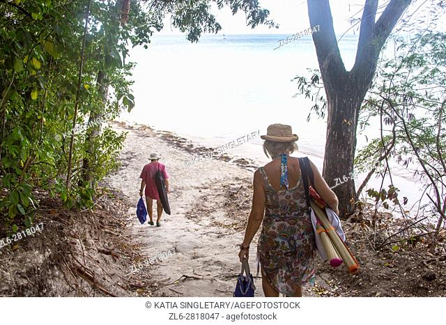 Older retired caucaisian couple going to the beach in the tropical island of Martinique