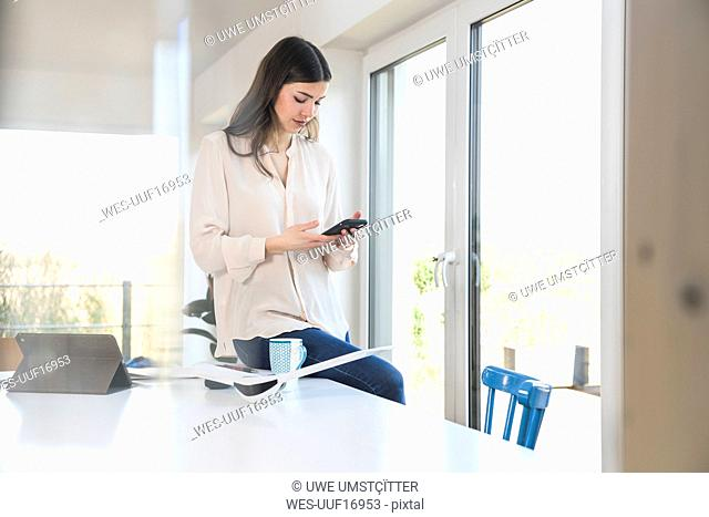 Young woman at table at home looking at smartphone