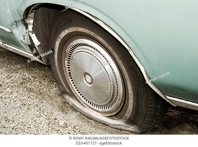 Flat tire on an old rusty 1979 Chrysler Cordoba car