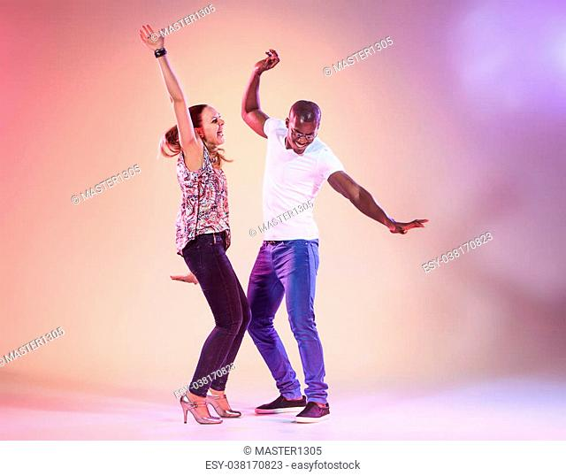 Young couple dances social Caribbean Salsa, studio shot on lilac background. Positive human emotions. The black african and caucasian models