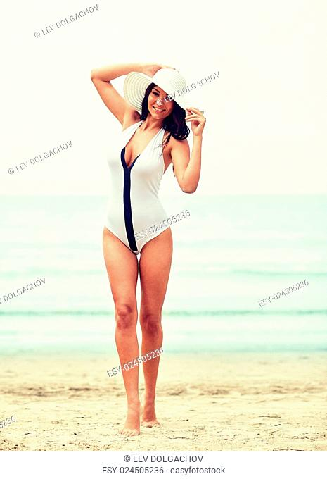 summer vacation, tourism, travel, holidays and people concept -young woman in swimsuit posing on beach