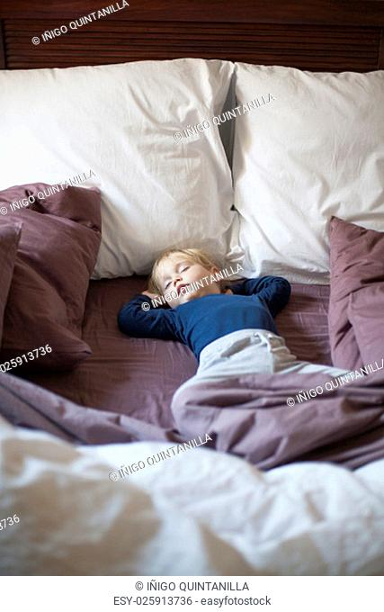 portrait of happy blonde caucasian baby nineteen month age with blue shirt sleeping in brown sheets bed between cushions