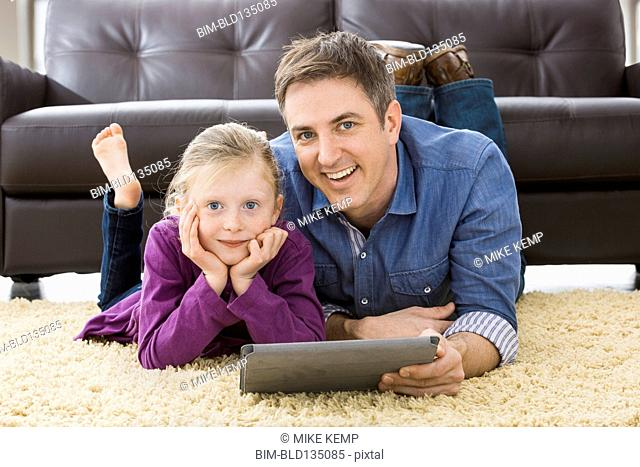 Caucasian father and daughter using tablet computer in living room