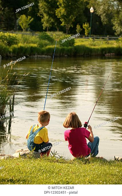 Boy And Girl Fishing On Lakeshore In The Midwest