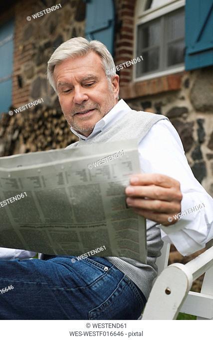 Germany, Kratzeburg, Senior man reading newspaper