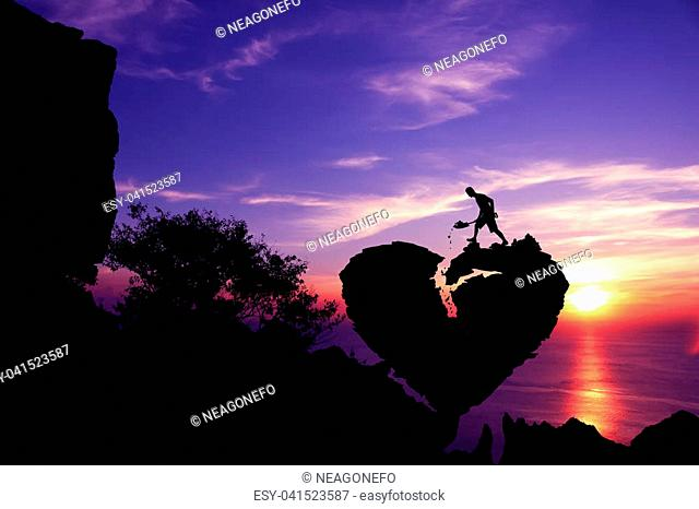 Man shoveling stone to repair the broken heart shape rock on the mountain with purple sky sunset.Silhouette Valentine background concept
