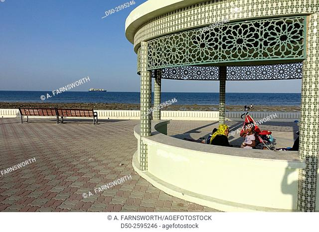 SUR, OMAN. Family on picnic outing on the corniche by the sea of Oman