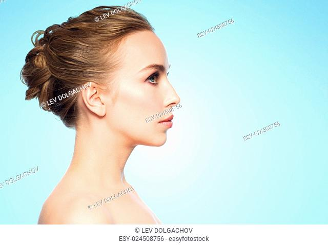 health, people, plastic surgery and beauty concept - beautiful young woman face over blue background