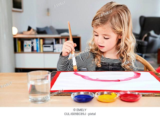 Young girl sitting at table, painting picture