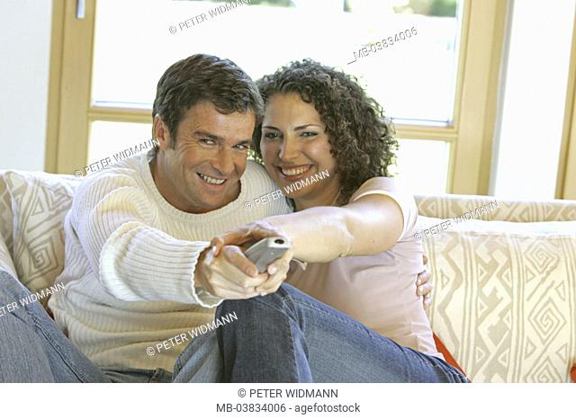 Living rooms, sofa, couple, smiling,  watches television, gesture, remote handling,   Series, 30-40 years, partnership, relationship, marriage, love